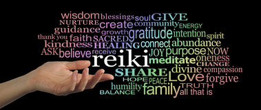 Sharing Reiki Word Cloud Website Header. Female hand facing upwards, gesturing towards the word reiki, which is floating off within a word cloud of healing words Stock Images