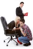 Sharing a secret. A young man who looks at a woman's purse who discuss something in secret with another young man royalty free stock photography