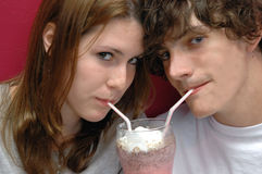 Sharing a sip. Two teens share a milkshake Royalty Free Stock Photo