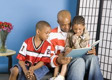 Sharing a story. Children being read a story by their father Stock Photo