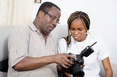 Sharing their love for photography. This men showshis photos that he tooks with his camera and asked the young woman's appreciations Royalty Free Stock Photo