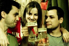 Sharing a toast in a pub. Two young men toast with their mugs of beers while a young woman hugs them with a big grin royalty free stock photography