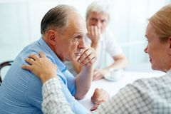 Sharing trouble. Senior men sharing his trouble with understanding friends who care Stock Photo