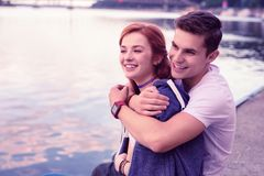 Strong smiling guy tightly hugging his pretty ginger girlfriend royalty free stock photography