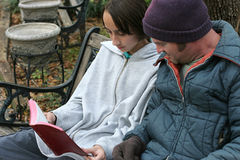 Sharing The Word. A teen volunteer reading the bible to a homeless person. Focus on the teen's face Royalty Free Stock Photography
