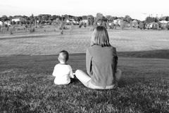 Sharing the world. A woman and a child sitting on a hill over looking a small town Stock Image