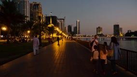 Sharjah, de V.A.E - 10 Mei, 2018: Europese toeristen met het lopen van kinderen op avonddijk Al Buheirah Corniche voorbij stock videobeelden
