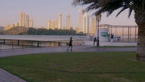 Sharjah, de V.A.E - 10 Mei, 2018: sportenmens die op ochtendquayside lopen langs Khalid-meer in de stad van Sharjah Mensen die lo stock video