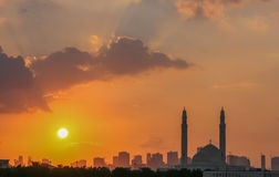 Sharjah mosque at sunset. Orange sunset over Sharjah city skyline with silhouetted mosque in foreground, United Arab Emirates Stock Photos