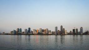 Sharjah Sommar 2016 Aftoncityscape med Persiska viken- och stadsarkitekturen arkivfoton