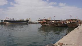 Sharjah, UAE - 13 de janeiro de 2018: Barcos de pesca que estão no molhe urbano em Sharjah, Emiratos Árabes Unidos, vista panorâm filme