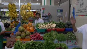 Sharjah, UAE - January, 2018: salesman selling fresh vegetables and greens at local food market in Sharjah city UAE. Sale vegetables and fruits on farm market stock video footage