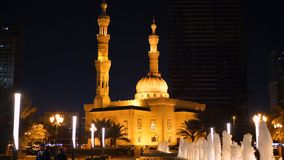 Sharjah UAE - Maj 10, 2018: nattspringbrunn och Al Taqwa Mosque med det härliga panelljuset in i den Sharjah staden i enigt stock video