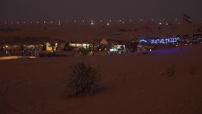 Sharjah, United Arab Emirates - January 15, 2018. Camp in desert. Jeep Safari excursion. Night view to pavilions. Illuminated with gold lights. Flag of UAE at stock video