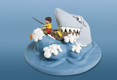 Shark Cake. Funny scene of a little fisherman in a boat, attacked by a huge shark. The scene is a cake, made of sugar fondant. Clipping path included Royalty Free Stock Image