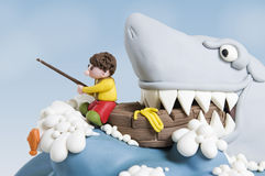 Shark Cake Close up. Funny scene of a little fisherman in a boat, attacked by a huge shark. The scene is a cake, made of sugar fondant stock photography