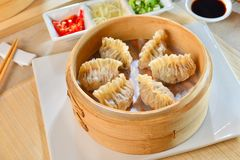 Shark fin dumplings in bamboo tray with chili and soyal sauce on Royalty Free Stock Image