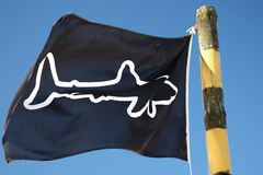 Shark Warning Flag. Flag with a shark emblem to warn swimmers at the beach Royalty Free Stock Photo