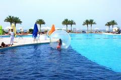 Sharm El谢赫,埃及- 2017年4月09日:一个可膨胀的气球的女孩,获得在水的乐趣 库存照片