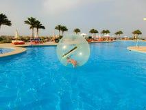 Sharm El谢赫,埃及- 2017年4月09日:一个可膨胀的气球的小女孩,获得在水的乐趣 免版税库存图片