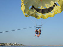 SHARM EL SHEIKH, ÄGYPTEN - 19. Juni 2015: Zwei Leute fliegen auf einen gelben Fallschirm Stockbilder