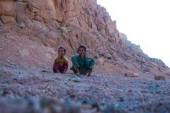SHARM EL SHEIKH, ЕГИПЕТ - 9-ОЕ ИЮЛЯ 2009 2 дет сидят в пустыне, и смотрят в расстояние Стоковое Изображение RF