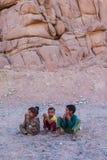 SHARM EL SHEIKH, ЕГИПЕТ - 9-ОЕ ИЮЛЯ 2009 3 дет сидят в пустыне, и смотрят в расстояние Стоковые Изображения