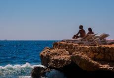 SHARM EL SHEIKH, EGIPTO - 9 DE JULHO DE 2009 Ideia traseira de um par romântico que senta-se nos vadios do sol que apreciam o mar fotografia de stock royalty free