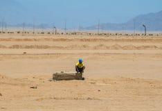 SHARM EL SHEIKH, EGIPTO - 9 DE JULHO DE 2009 um homem que senta-se no deserto Imagens de Stock