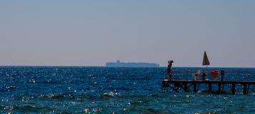 SHARM EL SHEIKH, EGIPTO - 9 DE JULIO DE 2009 la mujer se coloca en un embarcadero en la playa y mira los buques mercantes en la d Fotos de archivo libres de regalías