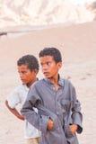 SHARM EL SHEIKH, EGIPTO - 9 DE JULIO DE 2009 Niño triste dos que se coloca en el desierto, y mirando en la distancia imagen de archivo