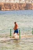 SHARM EL SHEIKH, EGIPTO - 9 DE JULIO DE 2009 un hombre que camina en el mar en un fondo de hoteles Fotografía de archivo