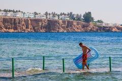 SHARM EL SHEIKH, EGIPTO - 9 DE JULIO DE 2009 un hombre que camina en el mar en un fondo de hoteles Fotografía de archivo libre de regalías
