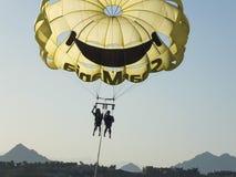 SHARM EL SHEIKH, EGIPTO - 19 de junio de 2015: Dos personas están volando en un paracaídas amarillo Fotos de archivo libres de regalías
