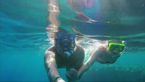 Sharm el Sheikh, Egipto, marzo de 2017: Un par joven está tirando un vídeo del selfie debajo del agua Nadada en el mar con a almacen de metraje de vídeo