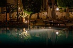 Sharm el-Sheikh, Egitto - 02 06 2018: la notte nello stagno dell'acquamarina dell'hotel ha piegato di legno vuoto degli ombrelli fotografia stock libera da diritti