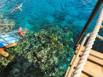 Sharm El Sheikh, Egypt - December 31, 2018: The people snorkeling in blue waters above coral reef on red sea in Sharm El royalty free stock photography