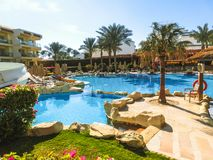 Sharm El Sheikh, Egypt - December 31, 2018: Tropical luxury Xperience Sea Breeze Resort on Red Sea beach. Swimming pool , water slide and poolside seating area stock photos