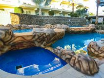 Sharm El Sheikh, Egypt - December 31, 2018: Tropical luxury Xperience Sea Breeze Resort on Red Sea beach. Swimming pool , water slide and poolside seating area stock photography