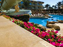Sharm El Sheikh, Egypt - December 31, 2018: Tropical luxury Xperience Sea Breeze Resort on Red Sea beach. Swimming pool , water slide and poolside seating area stock images