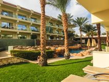 Sharm El Sheikh, Egypt - December 31, 2018: Tropical luxury Xperience Sea Breeze Resort on Red Sea beach. Swimming pool , water slide and poolside seating area stock image