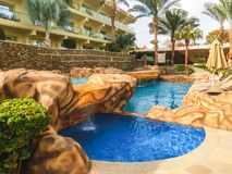 Sharm El Sheikh, Egypt - December 31, 2018: Tropical luxury Xperience Sea Breeze Resort on Red Sea beach. Swimming pool , water slide and poolside seating area royalty free stock photography