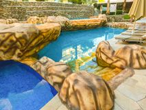 Sharm El Sheikh, Egypt - December 31, 2018: Tropical luxury Xperience Sea Breeze Resort on Red Sea beach. Swimming pool , water slide and poolside seating area royalty free stock image