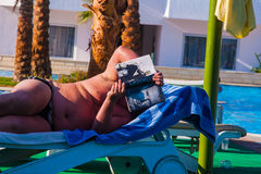 SHARM EL SHEIKH, EGYPT - JULY 9, 2009. A man on a deck chair reading a book Stock Image