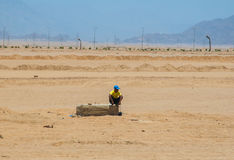 SHARM EL SHEIKH, EGYPT - JULY 9, 2009. a man sitting in the desert Stock Images