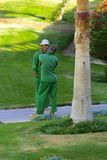 Sharm el-Sheikh, Egypt - March 14, 2018. Two gardener workers st. And on the hotel's alley and rest on the background of a bright short green grass royalty free stock photo