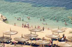 Sharm El Sheikh, Egypt May 07, 2019: people sunbathe on sun loungers under umbrellas on the beach and bathe in the sea in Egypt. Sharm El Sheikh, Egypt, May 07 royalty free stock photos