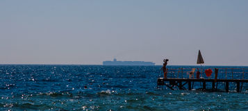 SHARM EL SHEIKH, EGYPTE - JULI 9, 2009 de vrouwentribunes op een pijler op het strand en bekijkt de koopvaardijschepen in de afst Royalty-vrije Stock Foto's