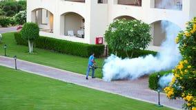 Sharm el Sheikh Egypten - April 5, 2018: Hotell Jaz Belvedere Man arbete som fördunklar för att avlägsna myggor med en sakkunnig arkivfilmer