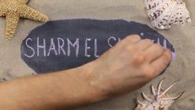Sharm el Sheikh manuscrito de la palabra escrito en tiza, entre conchas marinas y estrellas Visión superior almacen de video